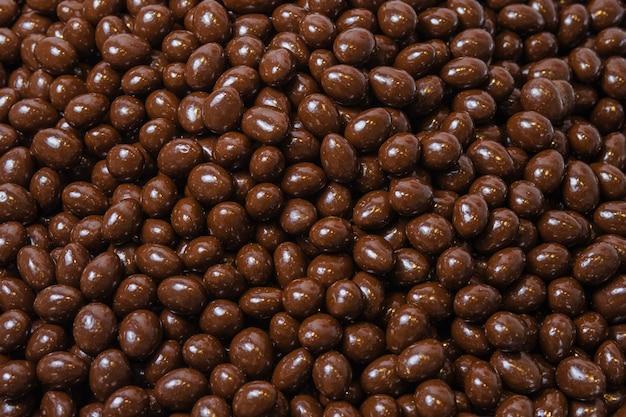 Коричневое драже, орехи в шоколаде, фон