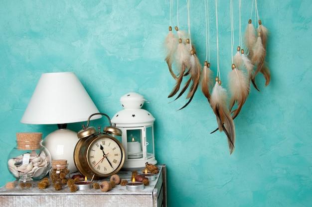 브라운 드림 캐처, 테이블 램프, 알람 시계 및 아쿠아 마린 질감 배경에 아로마 양초가있는 초라한 스탠드. 침실 장식.