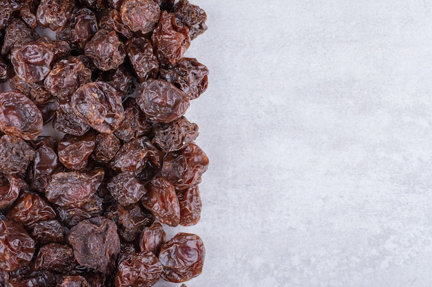 Brown dried cherries isolated on concrete surface