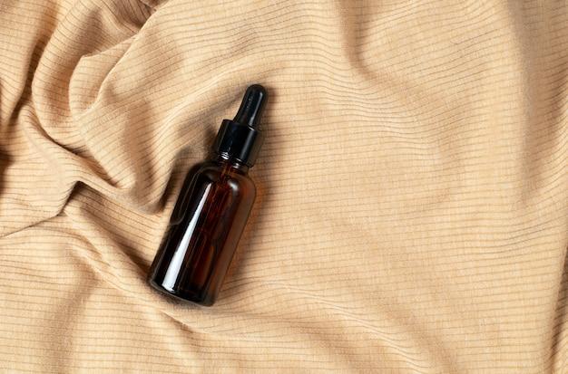 ベージュの生地にピペットが付いた茶色のスポイトガラス瓶。ゼロウェイストガラス容器。美容液、オイル、酸、ローション。オーガニックでナチュラルな化粧品。