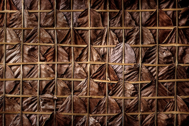 Brown dry leaves weave into the walls or roof of a country house.