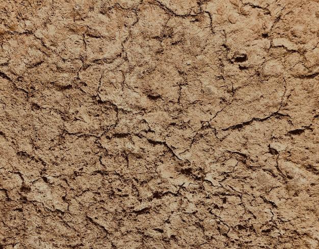 茶色の乾燥した土壌の背景上面では、土壌は砂漠の砂の水の蒸発の停滞をクラックし、水の蒸発による粘土土壌の地球温暖化の大きなクラック