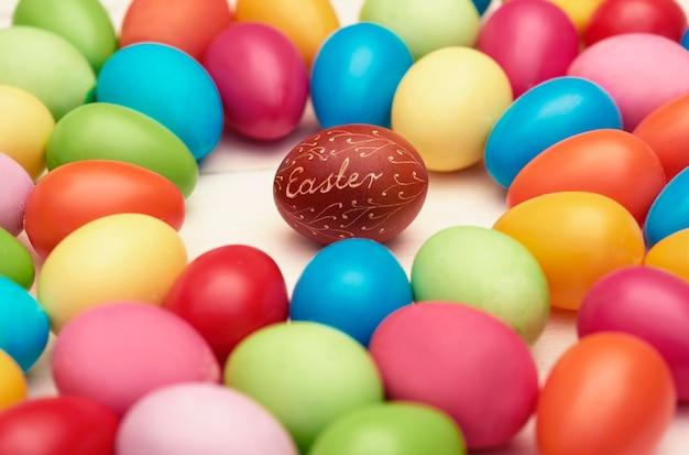 Uovo di pasqua marrone tra quelli colorati