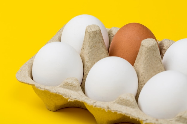 Brown egg among white eggs in box on yellow background