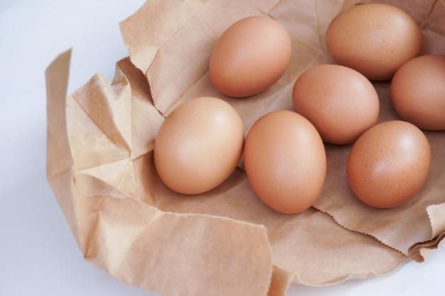 明るい色の背景、木のテーブルに新鮮な鶏の卵の後ろに紙袋に茶色の卵