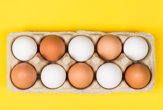 Brown eggs among white eggs in box on yellow background