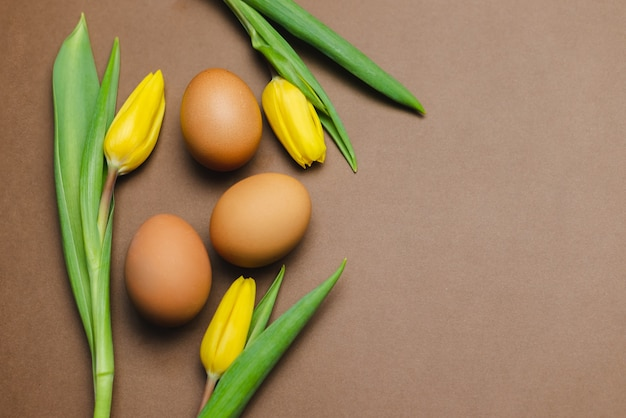 茶色のテーブルに茶色の卵と黄色いチューリップ。イースターテーブル