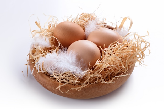 Brown eggs in a basket with lard and feathers.
