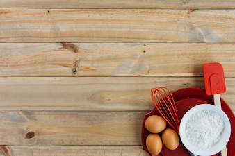 Brown eggs; flour and utensils on plate over wooden backdrop