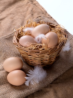Brown eggs in the hay in a nest with feathers. against the background of burlap. vertical.