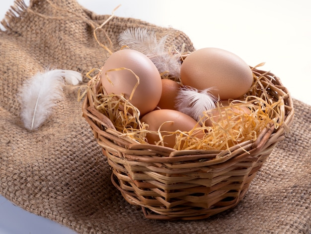 Brown eggs in the hay in a nest with feathers. against the background of burlap.