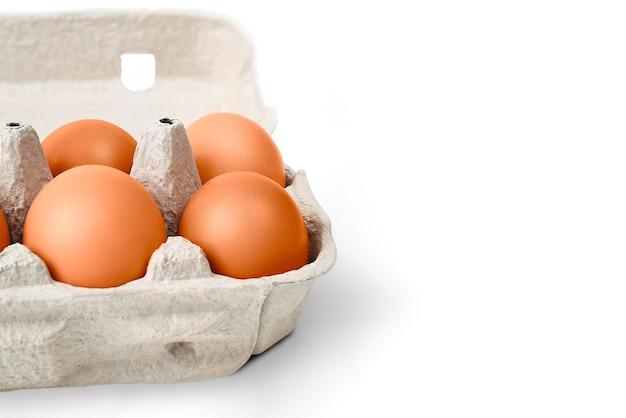 골판지 상자에 갈색 계란. 그림자와 흰 배경에 고립. 레이아웃, 레이아웃, 로고 및 텍스트 공간.