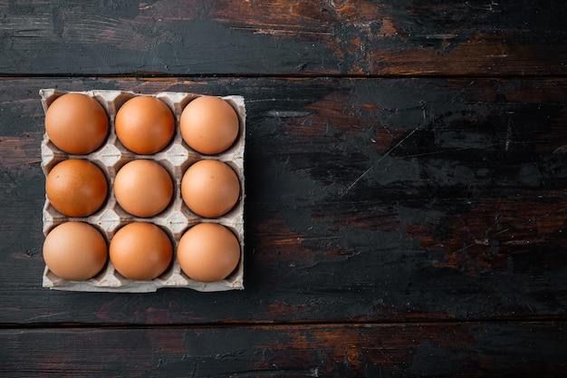 판지 상자 트레이 세트의 갈색 계란, 오래된 어두운 나무 테이블 배경, 위쪽 뷰 플랫 레이, 텍스트 카피스페이스를 위한 공간