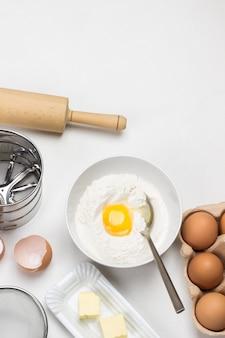 カートンコンテナ内の茶色の卵。皿にバターと泡だて器で。ボウルに小麦粉と卵黄。白色の背景。スペースをコピーします。フラットレイ