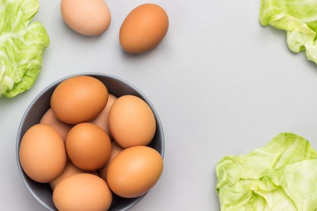 회색 세라믹 그릇에 갈색 계란. 양배추 잎과 테이블에 두 개의 계란. 공간 복사