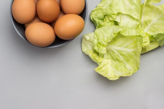 회색 세라믹 그릇에 갈색 계란. 양배추는 테이블에 나뭇잎. 공간 복사
