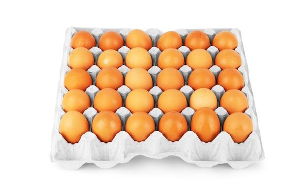 Коричневые яйца в бумажной упаковке на белом фоне