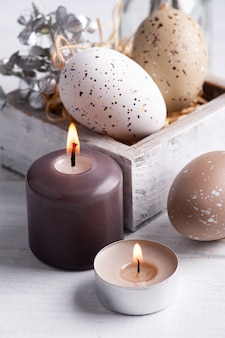 Brown eggs and lit candles in rustic easter composition on white wooden table. decoration in scandinavian style for greeting card