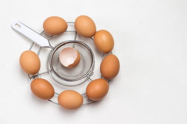 둥근 금속 스탠드에 갈색 계란. 계란은 원형으로 배열됩니다. 공간을 복사하십시오. 플랫 레이