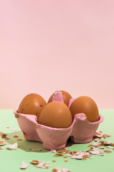 Brown eggs in rack with broken shell on green table