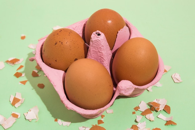 Brown eggs in rack with broken shell on table