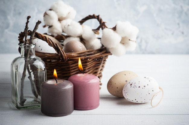 Brown eggs, wicker basket in rustic easter composition with lit candles on white wooden table.