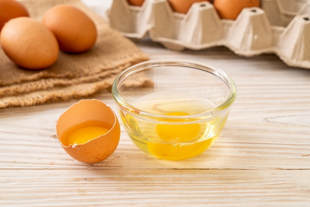 Brown eggs with one broken and egg yolk