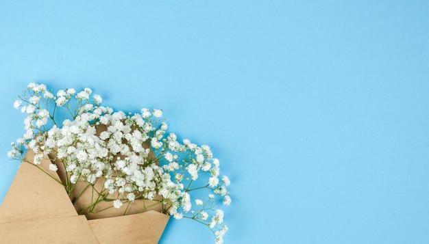 파란색 배경의 모서리에 배열 된 작은 흰색 라든지 꽃과 갈색 봉투