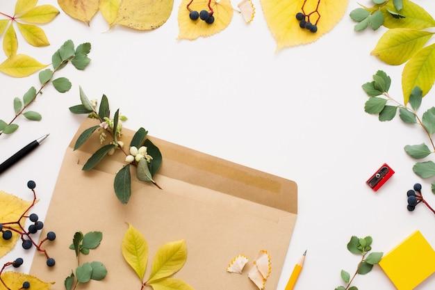 Коричневый конверт в рамке из осенних листьев, копией пространства
