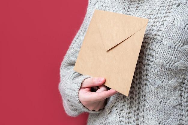 빨간색 배경에 여성의 손에 크래프트 종이로 만든 갈색 봉투, 클로즈업. 산타에게 보내는 편지, 위시리스트 컨셉입니다. 소녀는 편지를 들고 있습니다. 새 해 배경입니다.