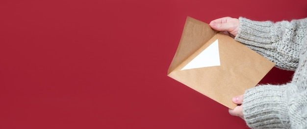 빨간색 배경에 여성의 손에 크래프트 종이로 만든 갈색 봉투, 클로즈업. 산타에게 보내는 편지, 위시리스트 컨셉입니다. 소녀는 편지를 들고 있습니다. 새 해의 배경, 배너, 복사 공간.