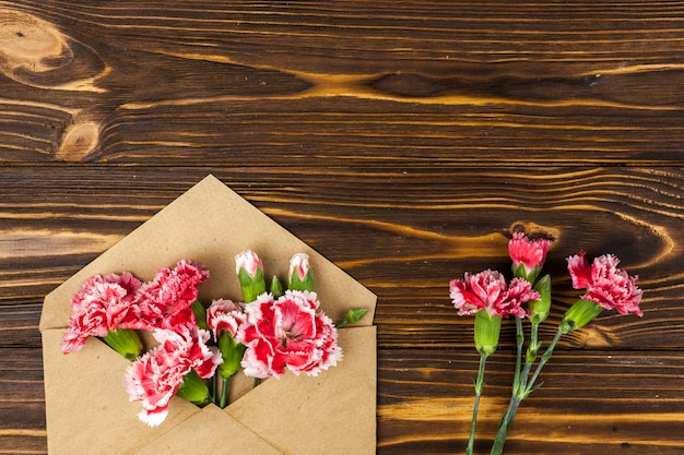 Brown envelope and red carnation flowers on wooden table