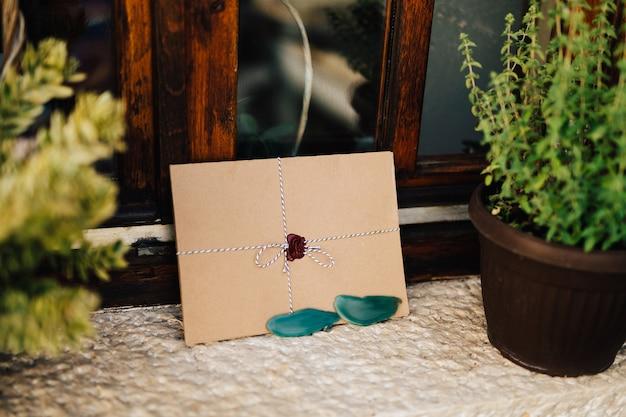 カラフルな紐で結ばれた茶色の封筒は、植木鉢の隣の白い窓辺にあります