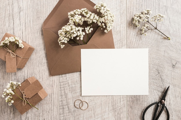 Brown envelope with baby's-breath flowers; gift boxes; wedding rings; scissor and white card on wooden background