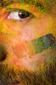 Brown eye of young homosexual man with bright colorful paint