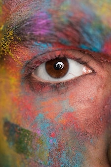 Brown eye of young man with bright colorful paint