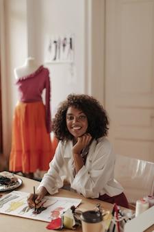 スタイリッシュな白いブラウスを着た茶色の目の美しい巻き毛の浅黒い肌の女性が机に座って、スタイリッシュな服と笑顔をデザインします