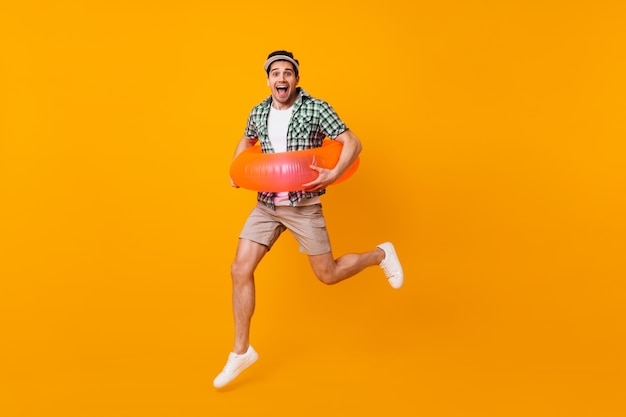 Brown-eyed brunet man in beige shorts and green t-shirt jumping with inflatable circle on orange space.