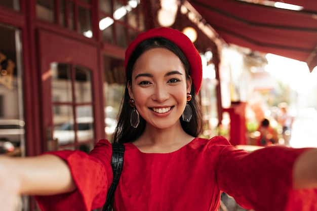 Brown-eyed brunette asian woman in red dress, bright beret and with stylish earrings smiles widely and takes selfie in street cafe