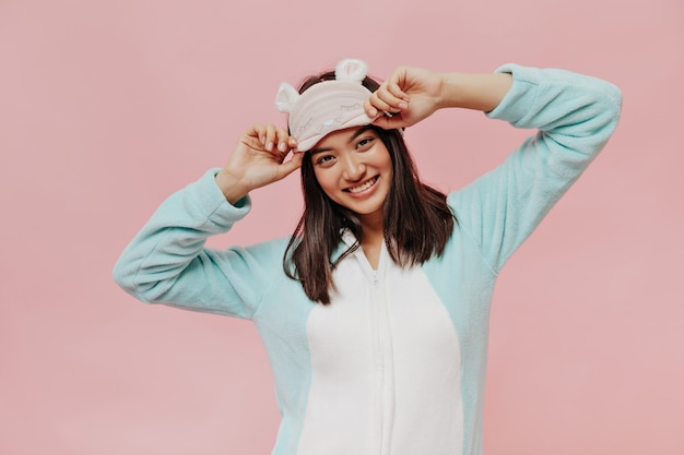 Brown-eyed brunette girl in cool mint soft pajamas puts on sleep mask and smiles sincerely on pink isolated wall