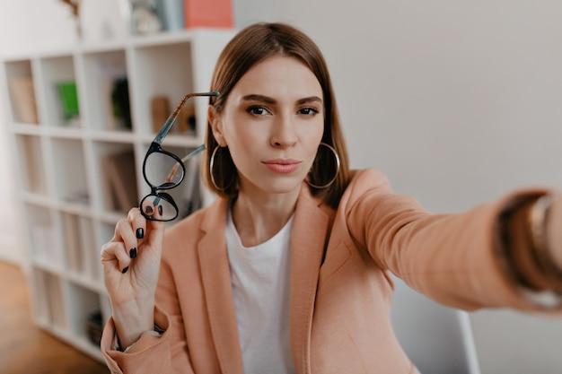 갈색 눈의 비즈니스 여성이 안경을 벗고 흰색 사무실에서 셀카를 찍습니다.