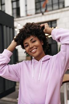 보라색 후드티를 입은 갈색 눈의 매력적인 곱슬 갈색 머리 여성은 진심으로 미소를 지으며 카메라를 바라보고 외부의 머리카락을 만집니다