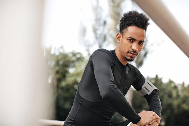 黒のtシャツとショートパンツを着た茶色の目の巻き毛の黒髪の浅黒い肌のスポーツマンがカメラをのぞき込み、公園でストレッチ