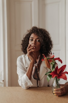 Brown-eyed curly brunette woman in white blouse and silk scarf touches face, looks at front and holds vase with red flowers