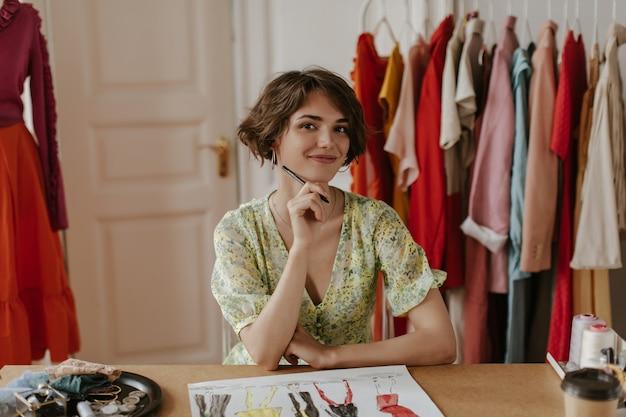 スタイリッシュな花柄のドレスを着た茶色の目の巻き毛の短い髪の女性は心から微笑んで、ペンを持って、ファッションデザイナーの居心地の良いオフィスでポーズをとる
