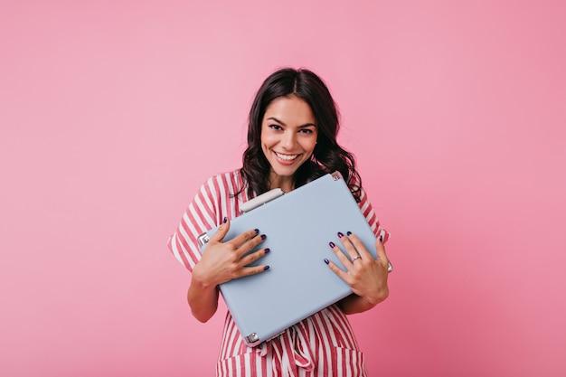 頬にくぼみのある茶色の目の浅黒い肌の少女は、レトロな青いブリーフケースでポーズをとって、ずる賢く微笑んでいます。