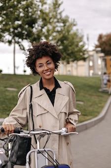 베이지색 트렌치 코트를 입은 갈색 눈의 검은 피부 여성이 진심으로 웃고 야외에서 자전거와 함께 포즈를 취합니다.