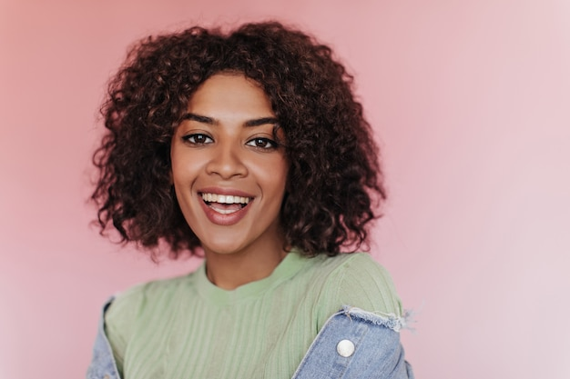 Кареглазая девушка в зеленой футболке с улыбкой позирует на розовой стене