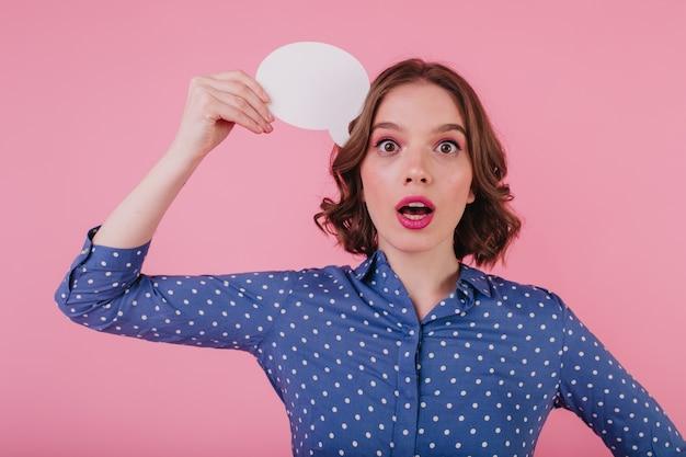 ピンクの壁に立っているウェーブのかかった髪の驚きの女性の屋内写真。