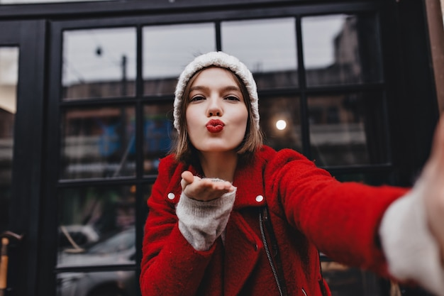 Кареглазая дама в белой шляпе посылает воздушный поцелуй. девушка с красной помадой делает селфи против окна.